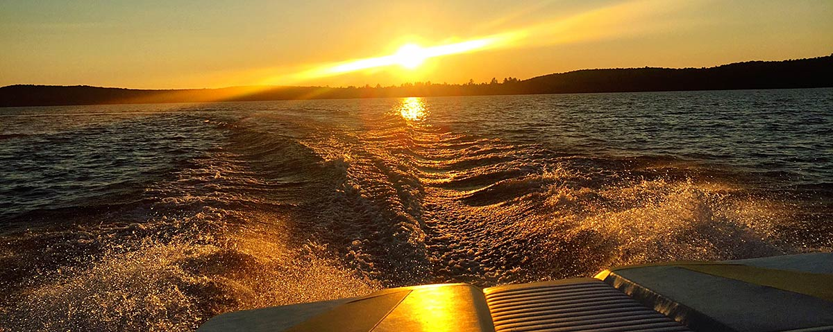 lake with wake from motor boat background image